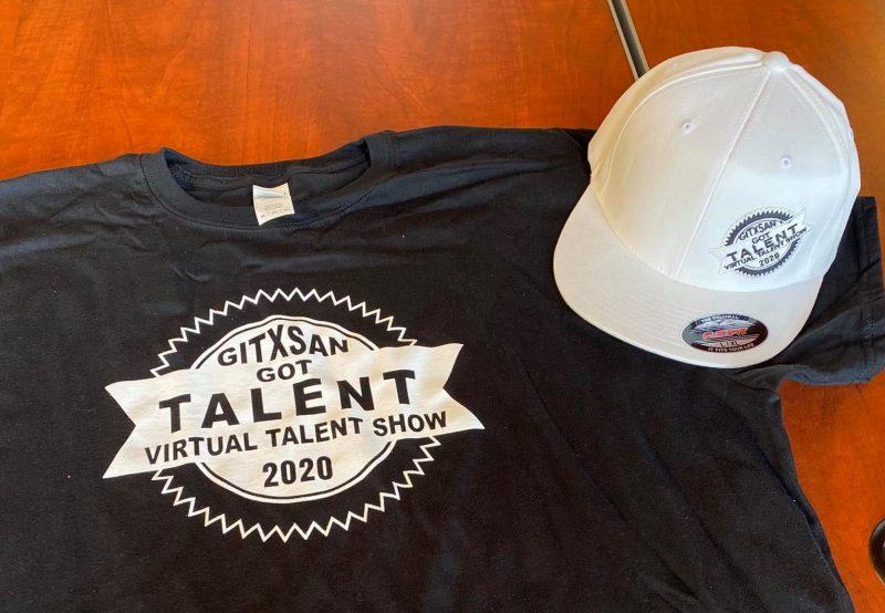 Casquette blanche et t-shirt noir imprimés avec le logo du concours. Il est écrit : Gitxsan Got Talent Virtual Talent Show 2020.