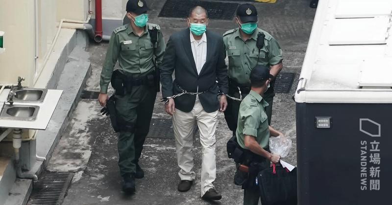 Le magnat des médias Jimmy Lai, menoté, traverse un couloir enchainé à deux policiers.