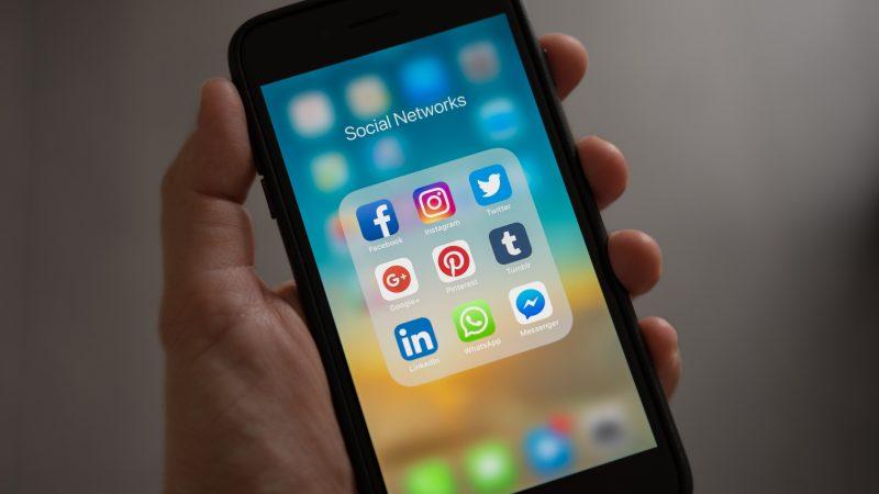 Un téléphone mobile sur lequel sont installés les principaux réseaux sociaux.