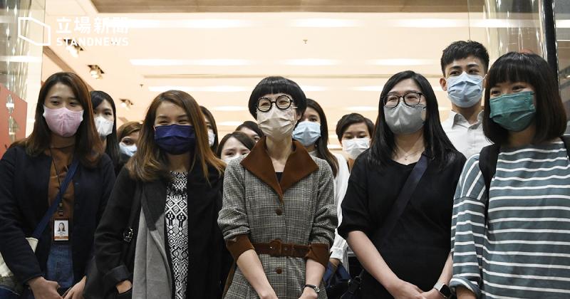 L'image montre une 15ne de personnes, d'origine asiatique. La majorité est constituée de jeunes femmes, portant un masque de protection faciale. Tous regardent face caméra. Ils se trouvent dans une pièce éclairée. En haut sur la gauche, on distingue le logo Standnews, avec une écriture en chinois et en anglais.