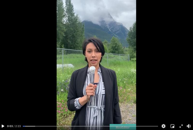 Cheyenne Raven se tient debout devant une montagne, avec un microphone à la main.