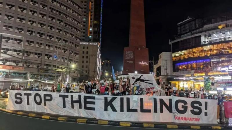 """Des manifestants tiennent une immense banderole sur laquelle est inscrit le slogan : """"Que les meurtres cessent!"""""""
