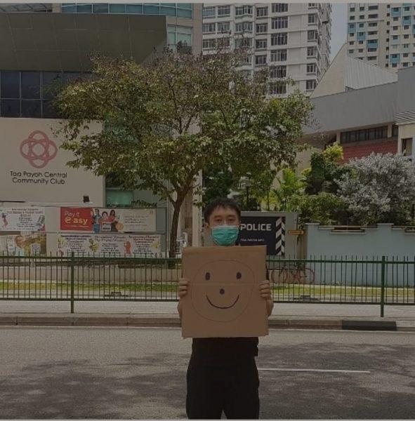 L'activiste Jolovan Wham tient une pancarte en carton. Il porte un masque et se trouve devant un poste de police, avec en fond des immeubles.
