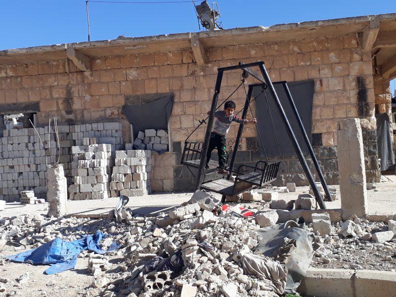 Un jeune garçon sur une balançoire au milieu des gravats à Deraa.