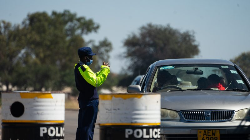 """Le policier porte un gilet réfléchissant et se tient entre deux tonneaux où l'on voit écrit : """"Police""""."""