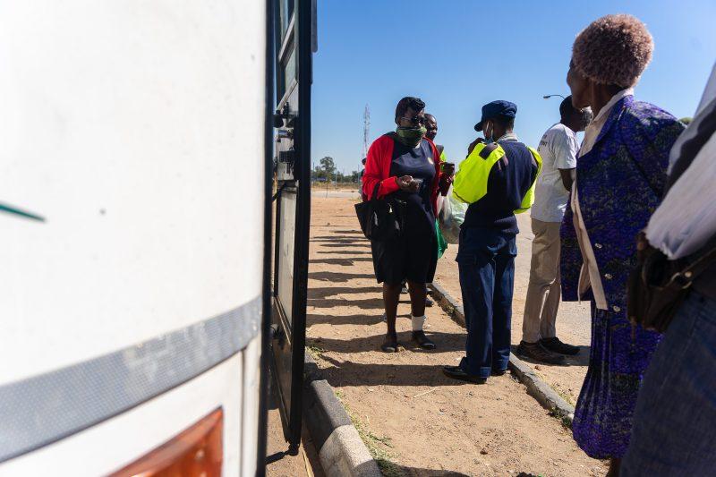 Des personnes patientent devant un bus. Un policier contrôle un passager
