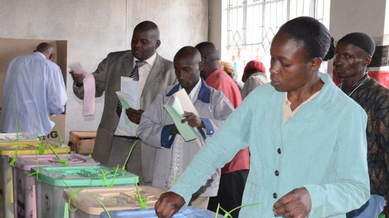 Une femme kényane en veste bleue dépose son bulletin dans l'une des urnes tandis que derrière elle, d'autres électeurs examinent leurs papiers.