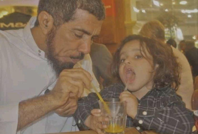 Salman al-Odah boit un jus de fruit à la paille dans le même verre que son petit-fils, dans un restaurant.