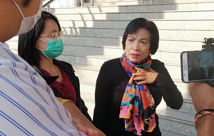 L'image montre 2 femmes et le profil d'un homme, thaïlandais. Au centre, la femme a été condamnée à de la prison au motif de crime de lèse-majesté. Elle est la seule à ne pas porter de masque de protection faciale. Son visage exprime à la fois de l'interrogation et de l'angoisse. Une autre personne filme la scène, et seules ses mains, tenant la caméra, sont visibles.