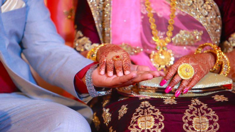 Un homme et une femme, lui en costume bleu, elle en sari brodé de fils d'or et les bras tatoués au henné, se tiennent main dans la main.
