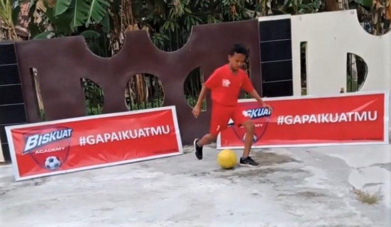 Un garçon en tenue rouge joue au football dans une cour en béton, devant des affiches de Biskuat Acedemy.