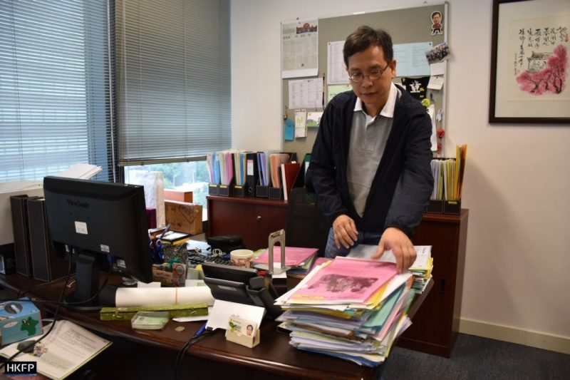 L'image montre Ip Kin-yuen, debout devant son bureau. Il est vêtu de manière décontracté. Il est sur le point de prendre un dossier sur lequel il porte les yeux. Les stores de sa fenêtre sont baissés. Son bureau est encombré de nombreux dossiers au côté d'un ordinateur. On aperçoit une étagère derrière lui. Sur le mur, il y a un cadre et un panneau sur lequel différentes notes sont accrochées.