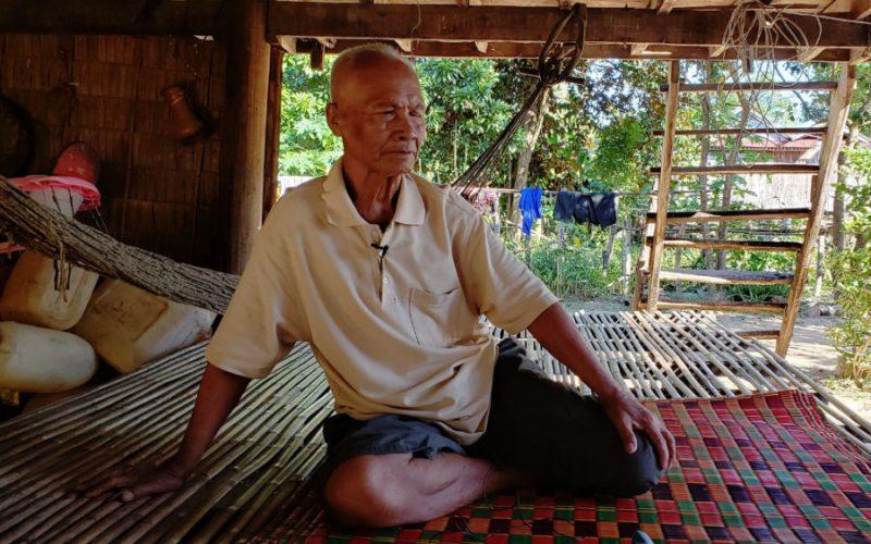 Un homme âgé, assis sur un tapis de sol. Il porte le regard sur le côté, et un micro est visible sur sa chemise (il est interviewé). Il est dans sa maison, dans une pièce ouverte sur les côtés. Un escalier de bois est visible, menant à l'étage. Il fait jour et le soleil brille.