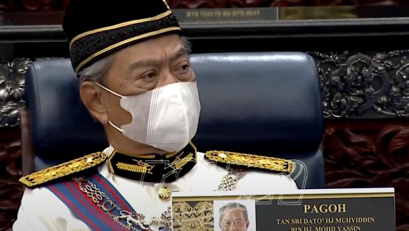 Le Premier ministre Muhyiddin Yassin porte un uniforme noir et or, et un masque de protection faciale, assis dans un fauteuil en cuir.