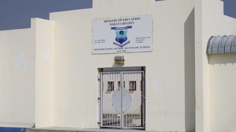 L'image est un plan sur l'entrée d'une école. On distingue une porte de style grillagé. Au dessus, on lit le nom de l'école. Le mur est blanc avec une bande bleue au bas du mur. On aperçoit un ciel bleu. On distingue à travers la porte un bâtiment avec des fenêtres ouvertes.