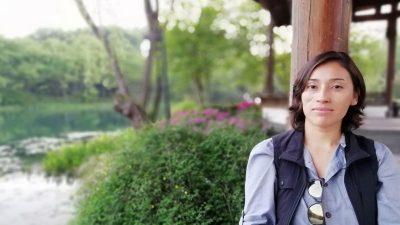Dr Patricia Castillo Briceño pose en chemise et veston, un demi-sourire aux lèvres, devant une rivière bordée d'arbres.