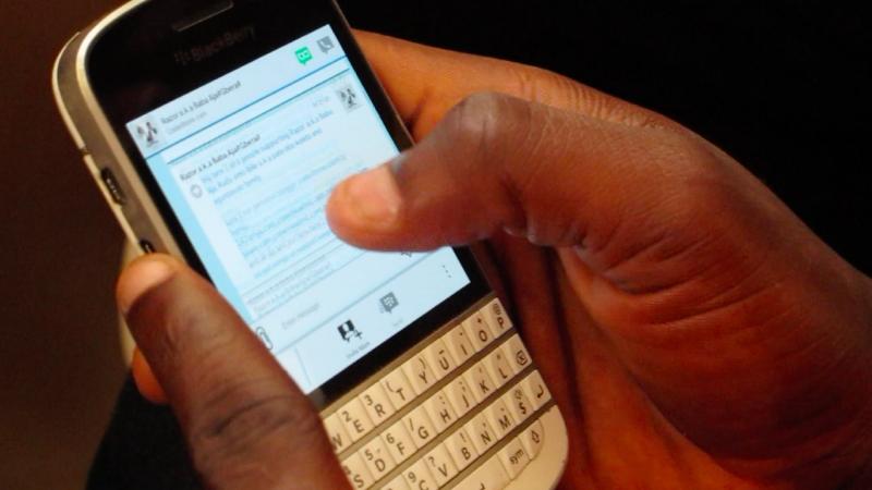 Les mains d'une personne noire tiennent un téléphone à clavier, s'apprêtant à répondre à un message.