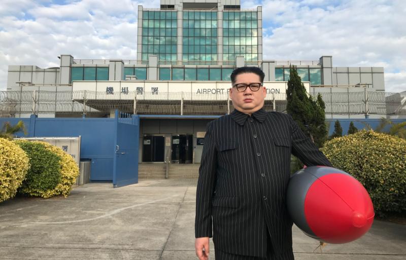 L'image montre un sosie de Kim Jong-un prendre la pose devant le bâtiment de la police aéroportuaire de Hong Kong. On peut lire l'enseigne en chinois et en anglais. L'homme tient un mini missile en plastique sous son bras. Il est habillé très sobrement d'une longue veste noire à rayures en fixant la caméra sans montrer la moindre émotion. Il porte des lunettes et des cheveux bruns coupés courts. Derrière lui, on distingue un portail bleu ouvert, donnant sur des escaliers puis sur les bureaux de la police aéroportuaire. Sur les côtés, il y a des rangées d'arbustes. Le ciel est nuageux.