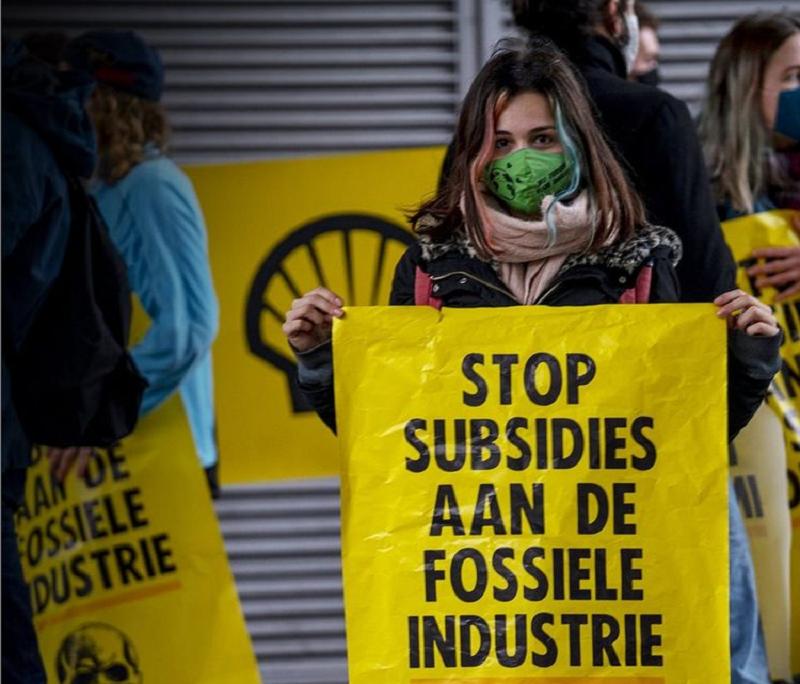 Une femme portant un masque vert tient une pancarte jaune sur laquelle est écrit en lettres majuscules noires, en néerlandais : Stop aux subventions aux énergies fossiles.