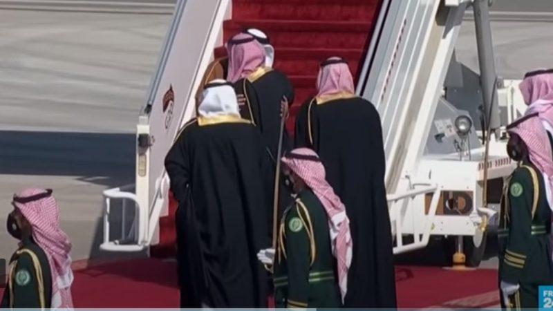 L'émir du Qatar descend de la rampe d'un avion, et étreint le prince héritier d'Arabie saoudite tandis que des gardes sont présents autour d'eux.