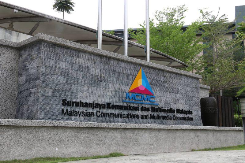 Façade en pierre montrant le logo de la MCMC, un triangle découpé en trois parties, ainsi que le nom de l'organisme en malais et en anglais.