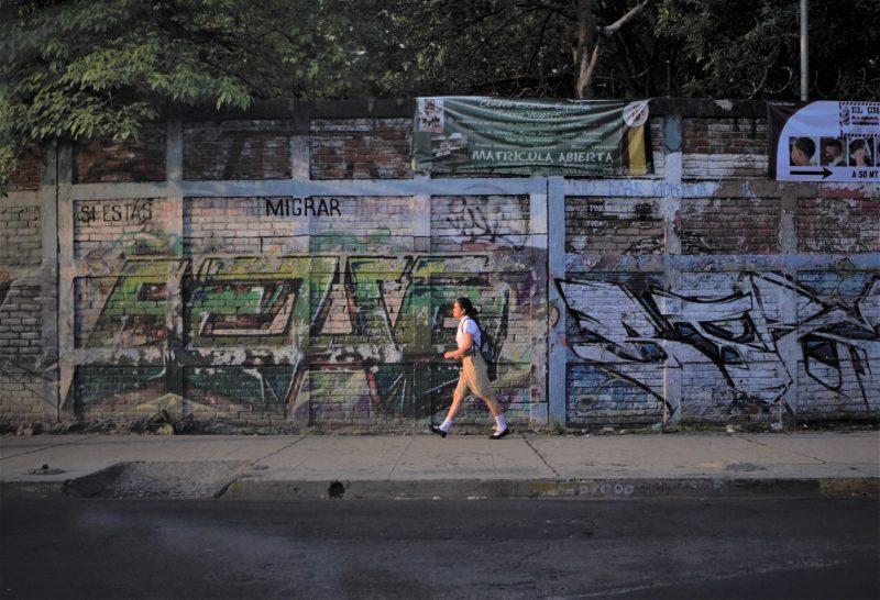 une écolière marche dans la rue, un mur tagué du mot Migrar derrière elle