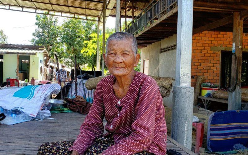 L'image montre une femme âgée assise sur un tapis de sol. Elle fait face à la caméra et a des cheveux courts. Elle est vêtue d'une tenue décontractée. Derrière elle, on distingue sa maison.