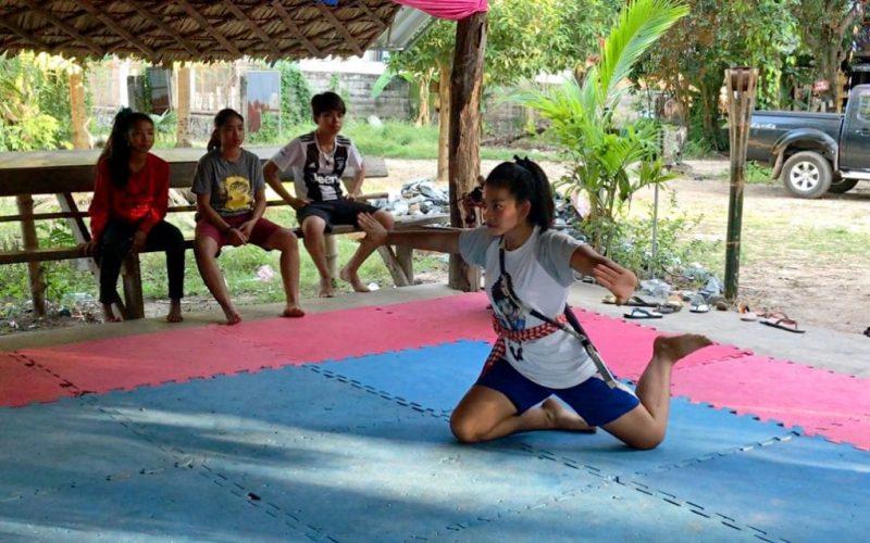 L'image montre une jeune fille, sur des tapis de sol, pratiquant un art martial. Elle est à genou, les bras levés et tendus sur les côtés. Elle tient un baton. Elle exécute une figure sportive. 3 autres jeunes gens, assis sur un banc sur le côté, l'observent. La scène se passe à l'extérieur, en journée. Le lieu est situé dans un cadre de verdure et est recouvert d'un toit, constitué vraisemblablement de bambous, il est ouvert sur les côtés.