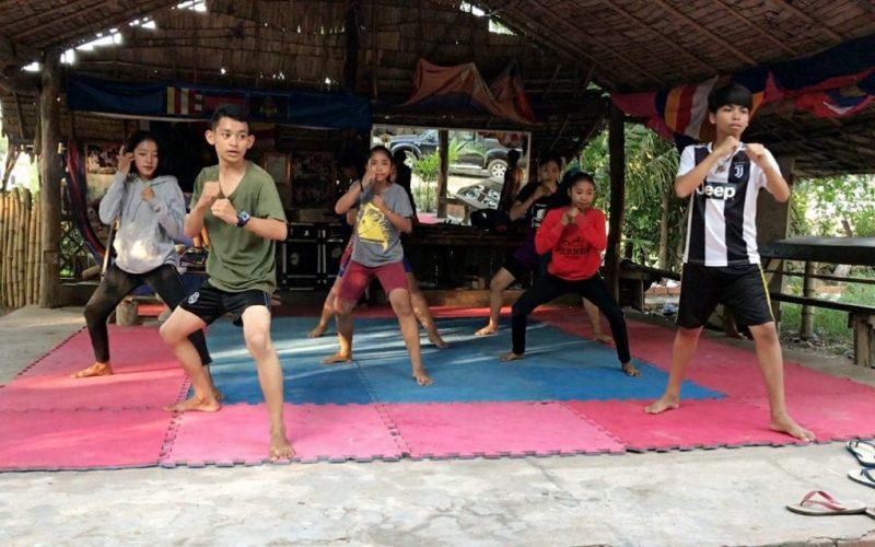 L'image montre 7 jeunes gens debout, sur des tapis de sol, en tenue sportive. Ils se tiennent tous dans une position de combat. La pièce est entièrement ouverte sur l'extérieur. Un toit fait, vraisemblablement, de bambous recouvre l'espace. Les tongs des jeunes gens sont visibles sur le côté.