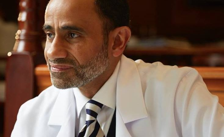Le Dr Walid Fitaihi, un homme d'âge mûr à la barbe grisonnante, pose dans un élégant costume blanc.