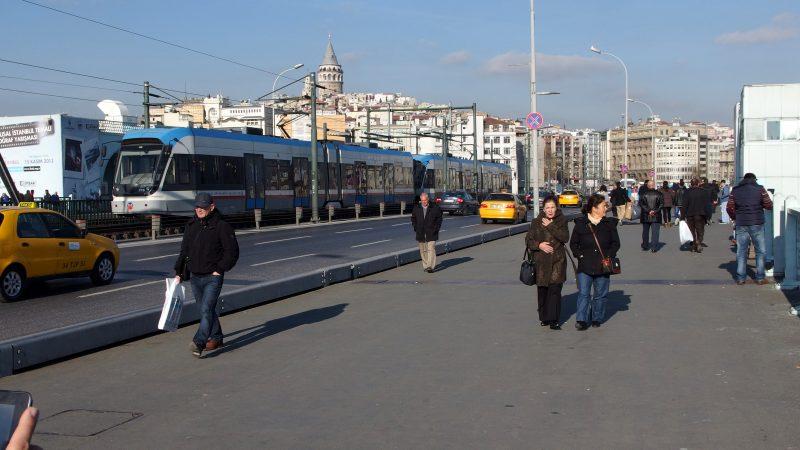 Une rue d'Istanbul avec une ligne de tram, une route où circulent des taxis, et un large trottoir.