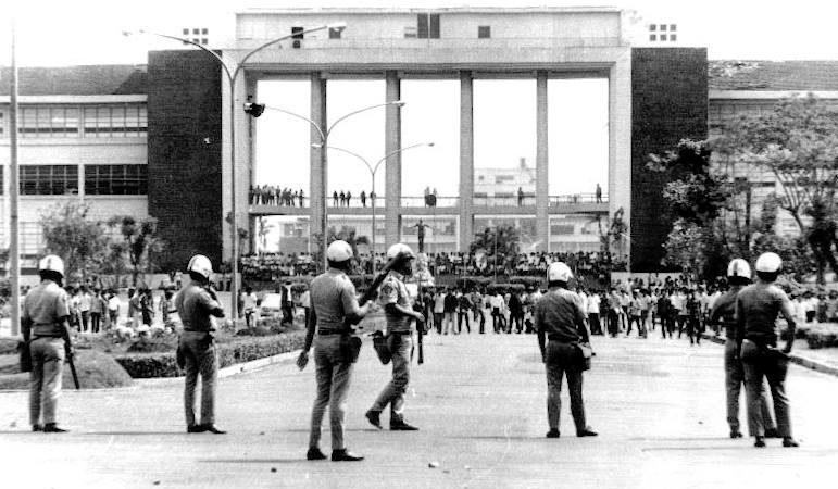 Photo en noir et blanc montrant quelques policiers armés devant l'entrée du Quezon Hall. Face à eux, un large groupe d'étudiants.