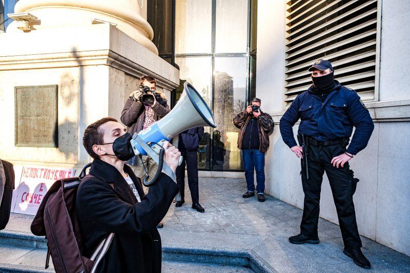 Une femme crie dans un mégaphone devant un immeuble devant deux journalistes