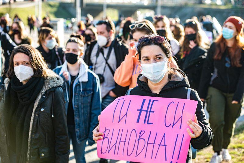 """Dans une foule aérée, une femme tient une banderole """"Tu n'es pas coupable""""."""