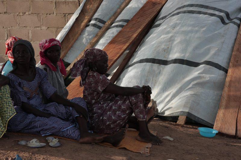 On aperçoit des femmes assises à même le sol, et en arrière plan ce qui semble être une tente.