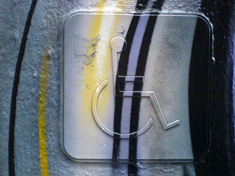 """Un panneau """"place réservée handicapé"""", avec le symbole d'un personnage en fauteuil roulant, est tagué de lignes noires, jaunes et mauves."""