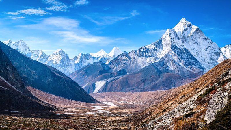 Les sommets enneigés du K2 se dressent à l'horizon, derrière un paysage à la végétation peu fournie.