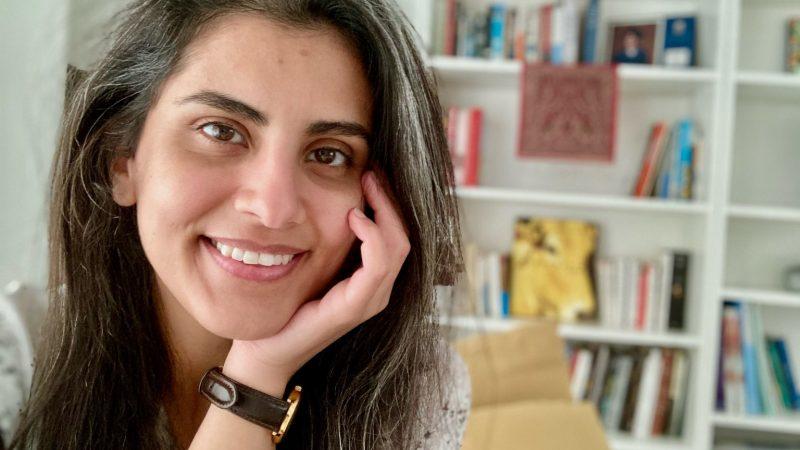 Plan serré sur le visage souriant de Loujain al-Hathloul devant une bibliothèque. Elle a les cheveux bruns détachés sur les épaules. Elle tient son visage avec sa main gauche.