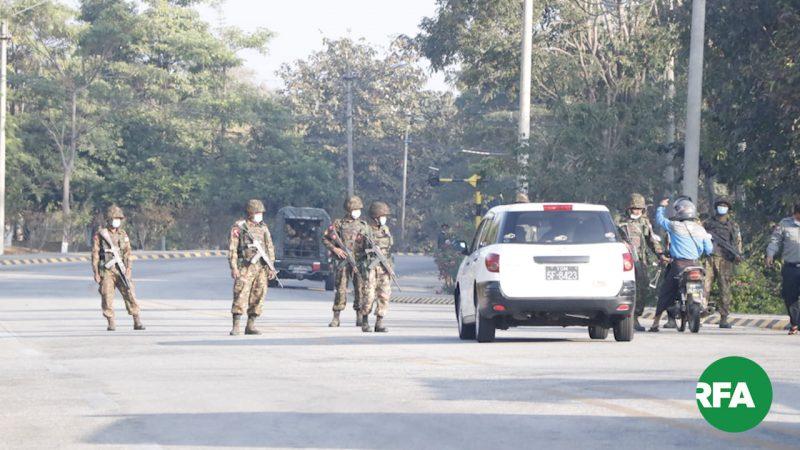 L'image montre une route sur laquelle on distingue des militaires avec masque facial. Ils sont positionnés au milieu de la route. Une voiture et un cyclomotoriste sont à l'arrêt, sur le côté droit de l'image. En arrière plan, on peut voir un véhicule militaire. Le logo RFA (Radio Free Asia), sur un fond vert, est visible en bas sur la droite de l'image. La scène se passe en journée, au soleil.