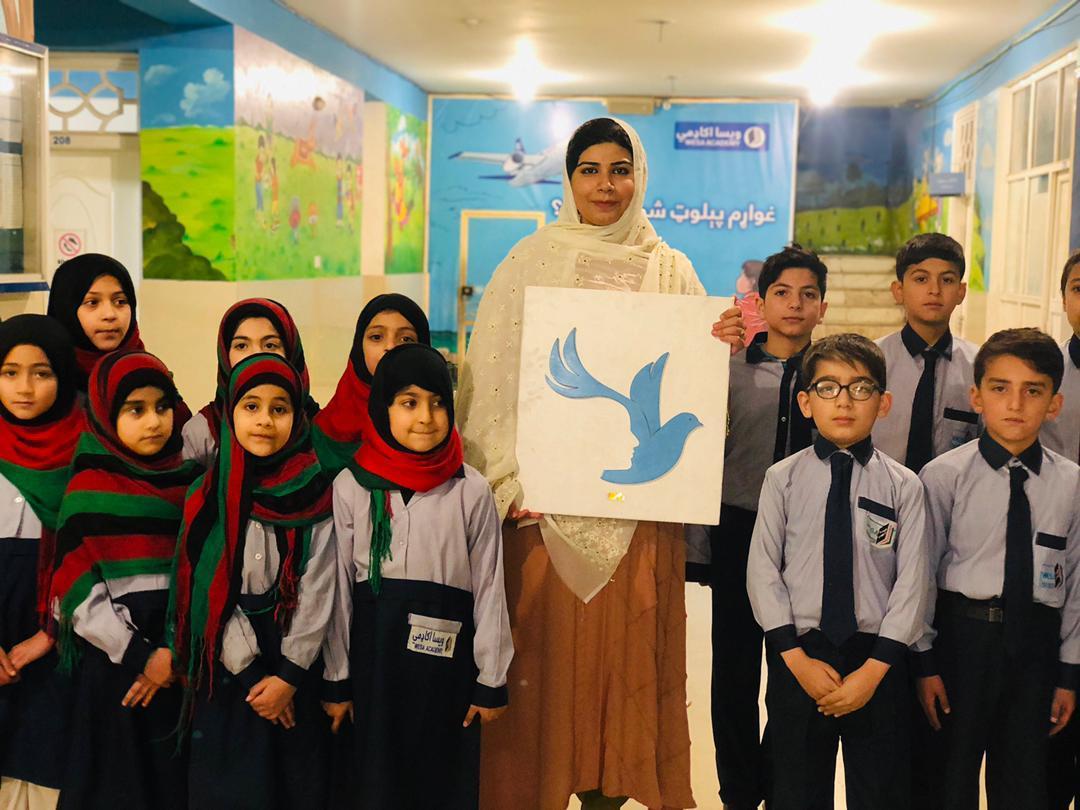 Mme Pashtana Zalmai Khan Durrani pose avec des élèves dans une structure scolaire