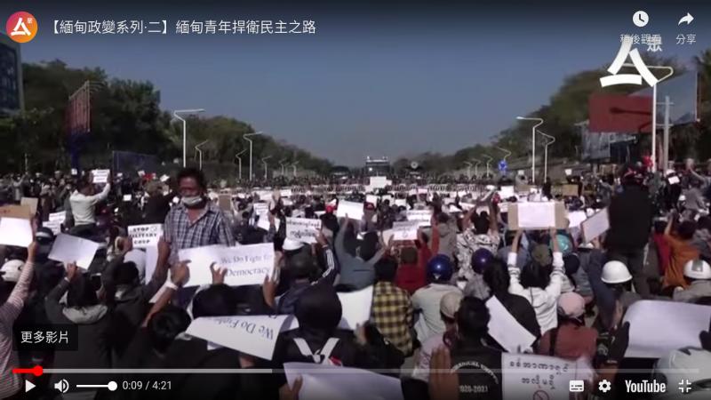 L'image montre, de dos, une foule compacte, manifestant dans la rue. Elle fait face aux militaires, postés en arrière plan. On distingue aussi des véhicules militaires. Les manifestants brandissent des pancartes avec des revendications en anglais et en birman.
