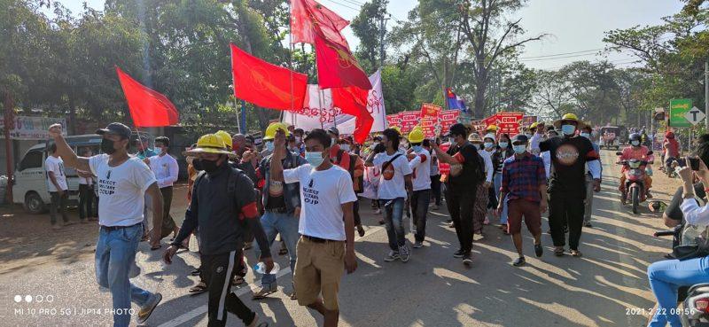 Des citoyens du Myanmar défilent dans la rue le poing levé, avec des drapeaux rouges, couleur de la NLD.