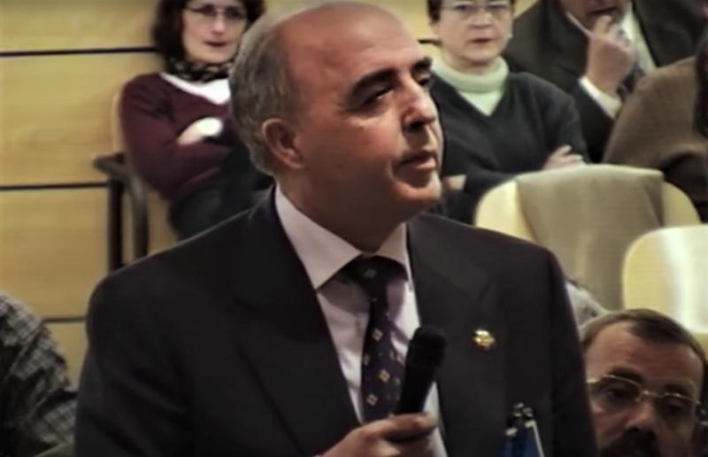 Enrique Rodríguez Galindo s'exprime à un micro devant un public. Il est âgé, le crane dégarni, en costume cravate.