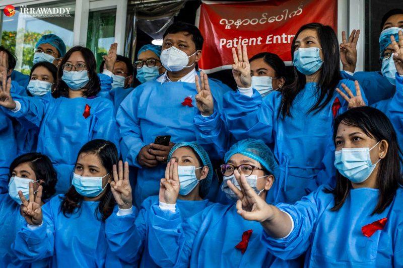 L'image montre un groupe de plusieurs medecins, hommes et femmes, en blouse bleue et portant un masque de protection faciale. Il font presque tous le salut à trois doigts. La plupart porte un ruban rouge sur le devant de leur blouse. Leur regard est légèrement tourné sur le côté, Ils se tiennent à l'extérieur devant l'entrée des urgences de leur hôpital. On distingue une banderole en anglais et en birman « Entrée des patients » (« Patient entrance »). Le logo du site « The Irrawaddy » apparaît en haut à gauche.