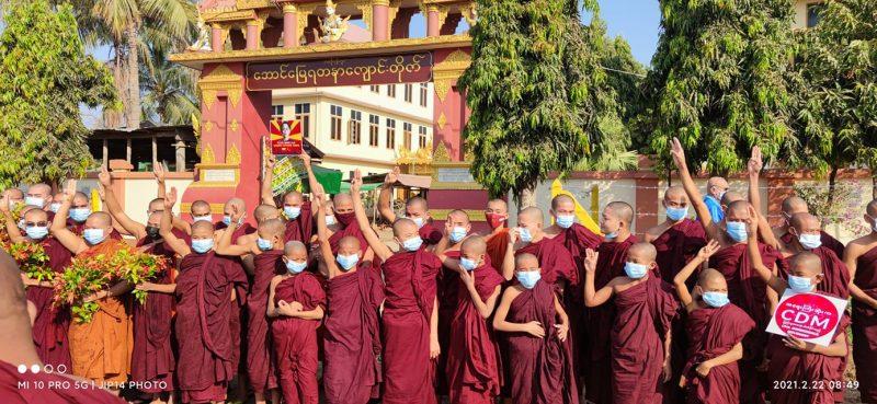 Un groupe de moines bouddhistes portant des masques font le salut à trois doigts devant l'entrée d'un monastère.
