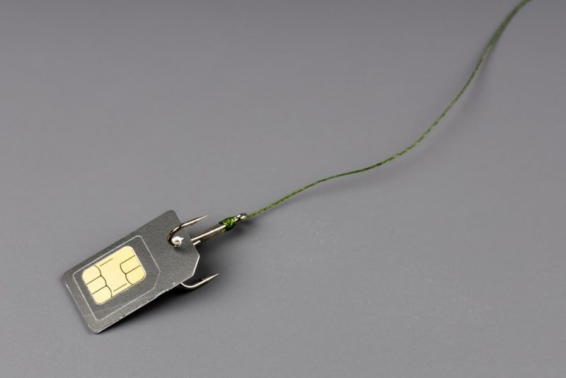 L'image est un plan serré d'une carte SIM, prise dans un hameçon, sur un fond nu, de couleur gris bleu.