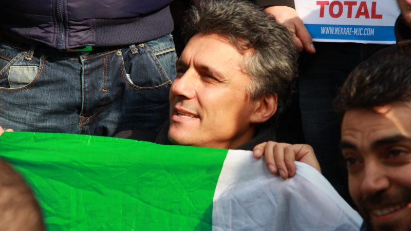 Rachid Nekkaz, un homme grisonnant, tient un drapeau vert et blanc au milieu d'une foule.