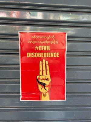 L'image montre une affiche collée sur une porte en fer. L'affiche, sur fond rouge, montre le salut à 3 doigts avec une inscription en birman et un hastag en anglais, « #civil disobedience » (désobéissance civile).