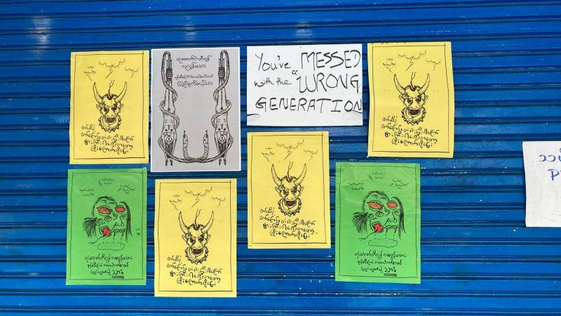 L'image montre 8 affiches collées sur une porte en fer bleue. Elles représentent des caricatures accompagnées de textes en langue birmane. Sur l'affiche, en blanc, située au milieu, on peut lire « You messed with the wrong generation » (« Vous vous êtes embrouillés avec la mauvaise génération »). 4 affiches identiques, sur fond jaune, sont le dessin d'une tête avec des cornes, faisant penser au mal, et portant un collier avec, en guise de perles, des têtes de mort. Au dessus de son crâne ouvert, il y a des nuages et des éclairs. 2 autres dessins identiques, sur fond vert, montrent un visage à 3 faces : une face qui rigole, une autre qui tire une langue de serpent, et une face qui est représentée avec des dents de vampire. Une dernière affiche, sur fond grisé, montre 2 corps féminins nus suspendus par les pieds, attachés par une corde. On aperçoit aussi 2 serpents enroulés autour de ces corps.
