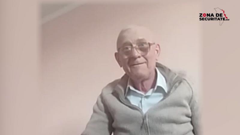 Plan moyen d'un homme âgé de type caucasien. Il porte des lunettes et a les cheveux blancs. Il est vêtu d'une chemise blanche et d'un gilet gris. En haut sur la droite, on distingue le logo « Zona de securitate.md » (site web moldave en langue roumaine, scrutant les violations des droits humains en Transnistrie).